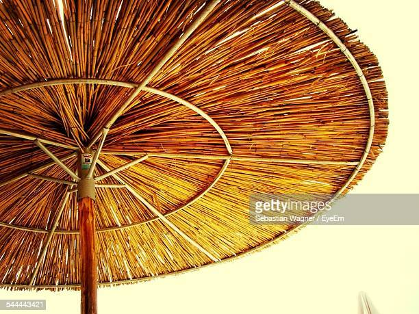 Low Angle View Of Thatched Roof Parasol Against Clear Sky