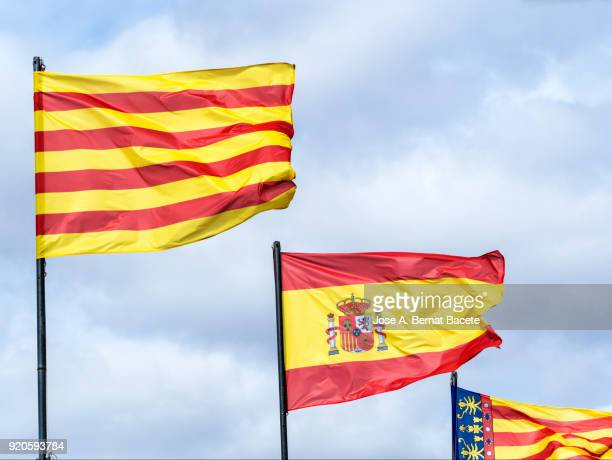low angle view of the flag of spain, the community of valencia and the (señera), against sky. spain - catalonia stock pictures, royalty-free photos & images