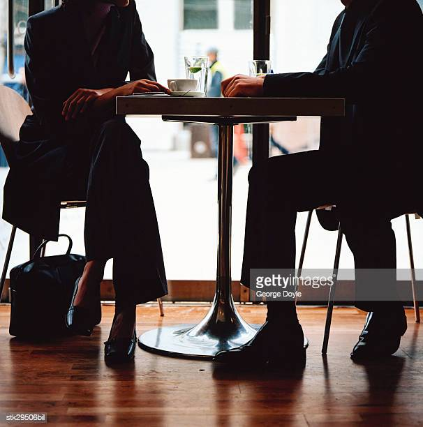 low angle view of the legs of a man and woman sitting at a caf?
