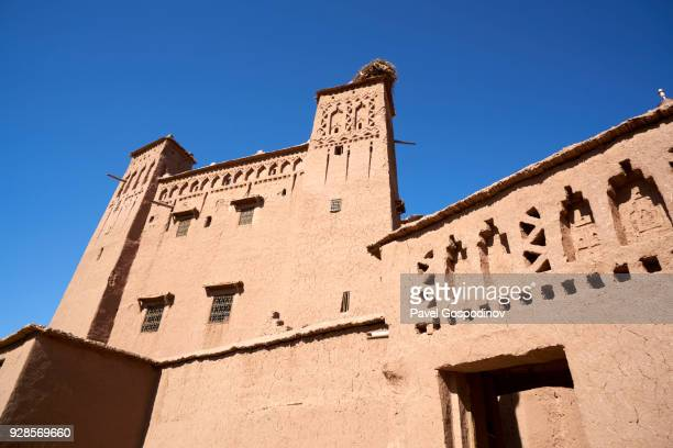 low angle view of the main facade of aït benhaddou, the unesco-protected red mudbrick ksar (kazbah) in saharan morocco - れんが造りの家 ストックフォトと画像