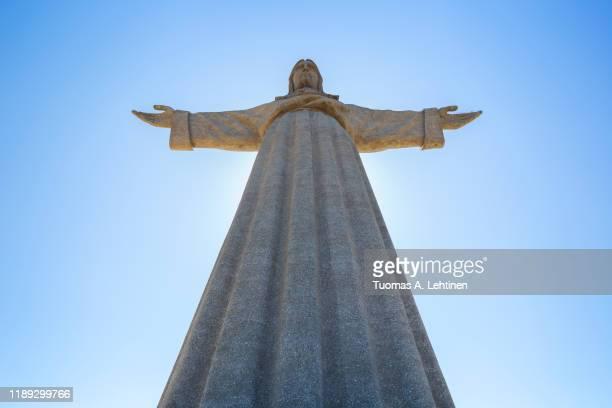 low angle view of the sanctuary of christ the king (santuario de cristo rei). it is a catholic monument of jesus christ in almada, portugal. - statua di cristo re foto e immagini stock