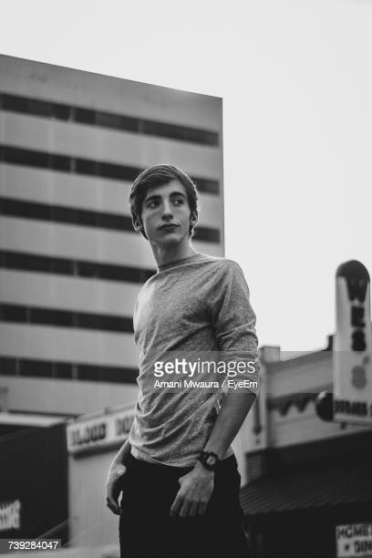 Low Angle View Of Thoughtful Man Looking Away While Standing Against Buildings