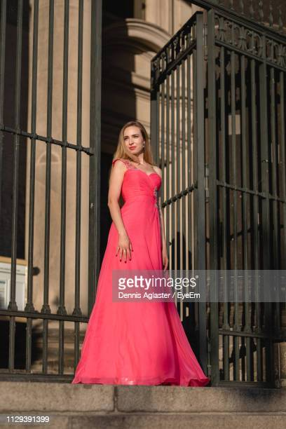 Low Angle View Of Thoughtful Woman In Pink Evening Gown Standing At Doorway