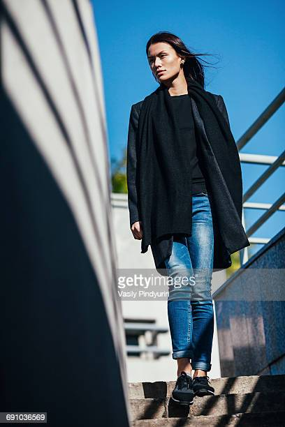 Low angle view of thoughtful woman standing on steps during sunny day