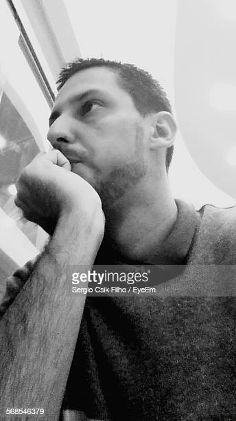 low angle view of thoughtful young man with hand on chin at home - filho stockfoto's en -beelden