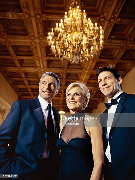 Low angle view of three people standing and smiling