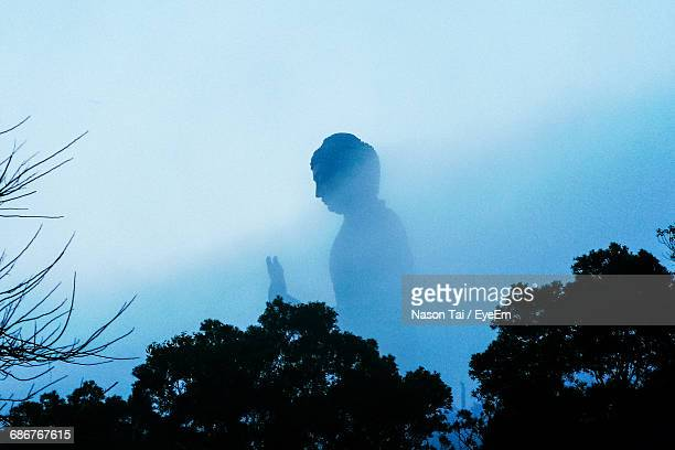 Low Angle View Of Tian Tan Buddha In Foggy Weather