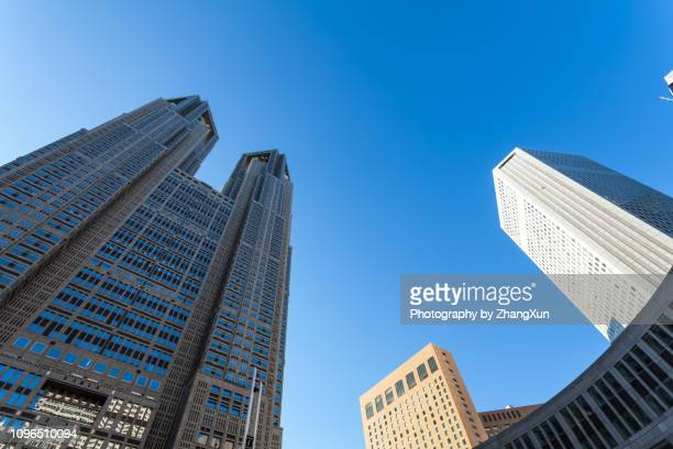 low angle view of tokyo metropolitan government building in shinjuky ward with blue sky as background, tokyo, shinjyuku, japan at day time. - 東京都庁舎 ストックフォトと画像