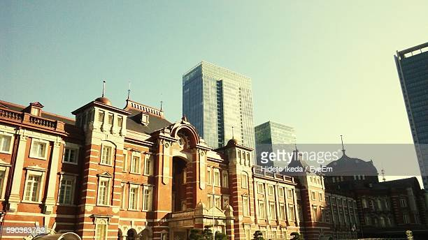 low angle view of tokyo station and buildings against clear sky - tokyo station stock photos and pictures