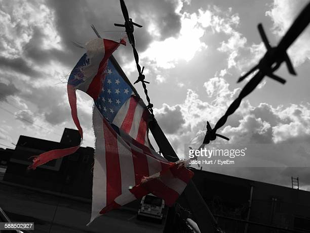 Low Angle View Of Torn American Flag Stuck In Barbed Wire Against Cloudy Sky
