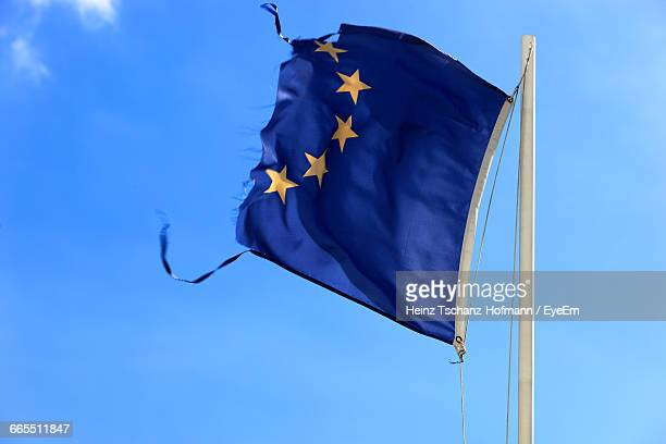 low angle view of torn european union flag against sky - european union flag stock photos and pictures