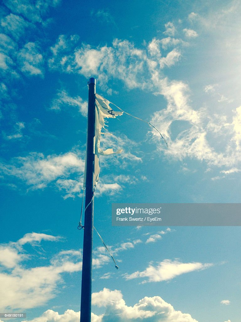 Low Angle View Of Torn Flag On Pole Against Sky : Stock-Foto