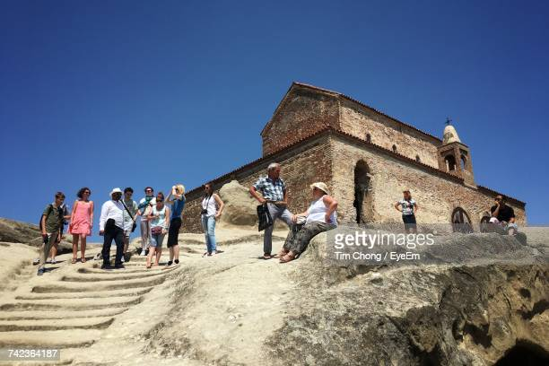 Low Angle View Of Tourist At Uplistsikhe Cave Against Clear Blue Sky