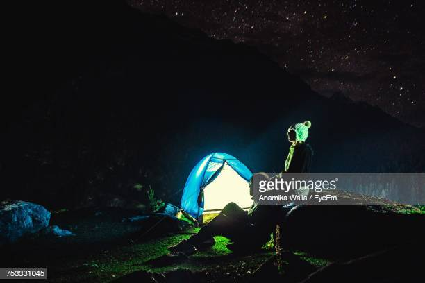 Low Angle View Of Tourists Looking At View At Night