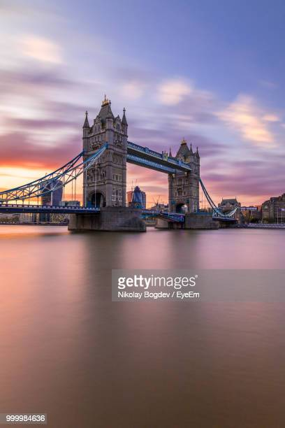 Low Angle View Of Tower Bridge Over River Against Cloudy Sky At Sunset