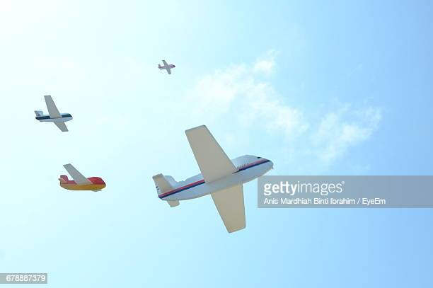 Low Angle View Of Toy Planes Flying Against Sky