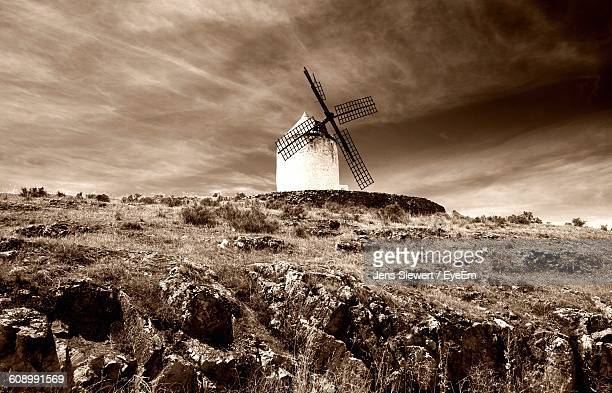 Low Angle View Of Traditional Windmill On Hill Against Cloudy Sky