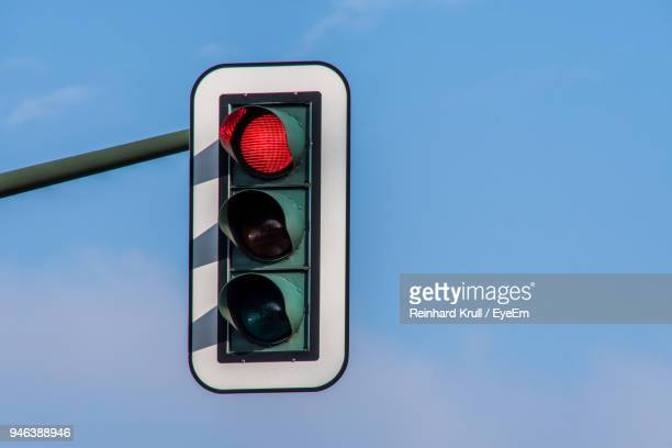 low angle view of traffic signal against blue sky - red light stock pictures, royalty-free photos & images