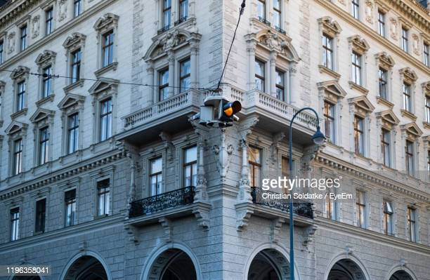 low angle view of traffic signal against building - christian soldatke stock pictures, royalty-free photos & images