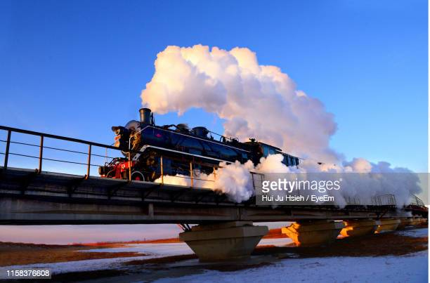 low angle view of train emitting smoke against sky - steam train stock pictures, royalty-free photos & images