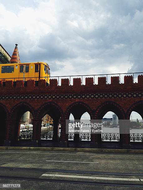Low Angle View Of Train On Bridge Against Cloudy Sky