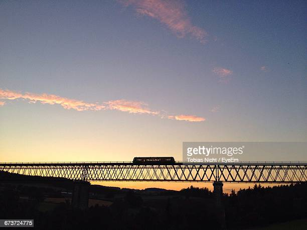 Low Angle View Of Train On Silhouette Bridge Against Sky During Sunset