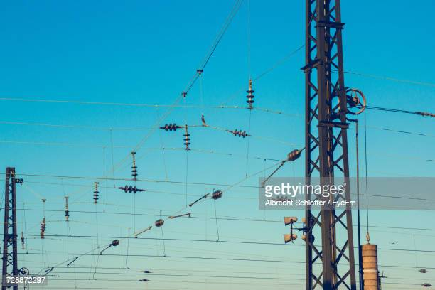 low angle view of transformers on cable against blue sky - albrecht schlotter stock-fotos und bilder