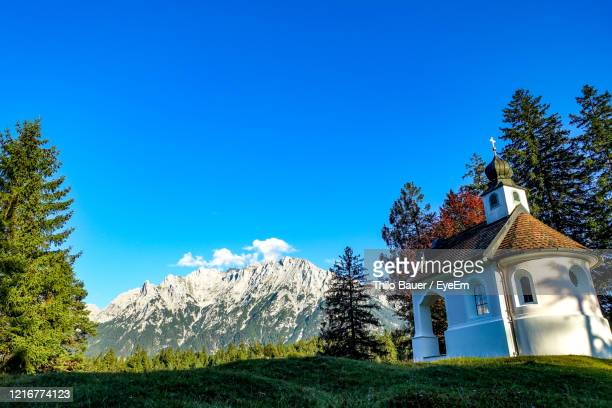 low angle view of trees and building against blue sky - mittenwald stock pictures, royalty-free photos & images