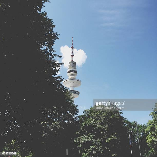 low angle view of trees and heinrich-hertz-turm against sky - hertz stock pictures, royalty-free photos & images