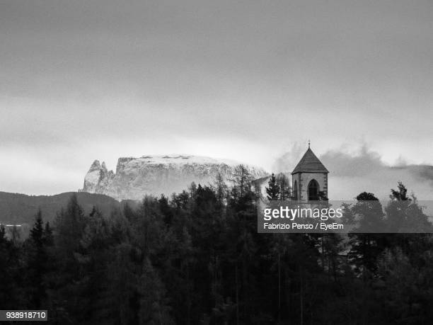 low angle view of trees growing by church and mountains against sky - fabrizio penso foto e immagini stock