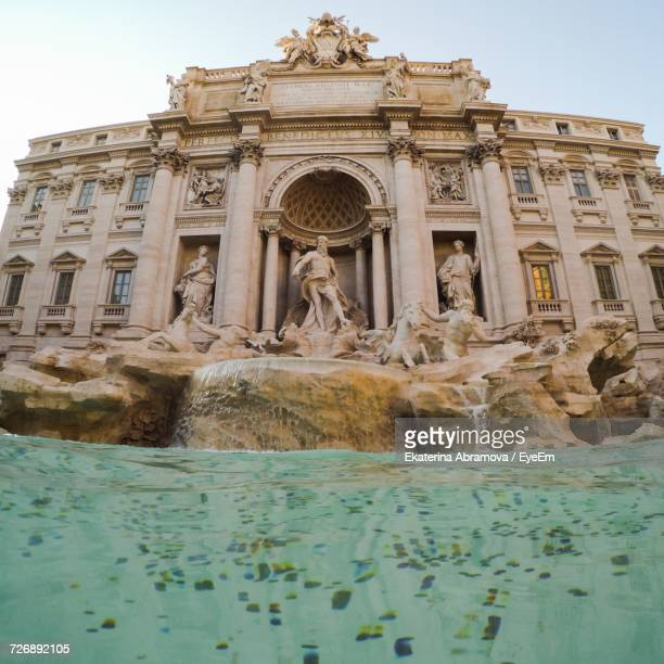low angle view of trevi fountain against sky - trevi fountain stock photos and pictures