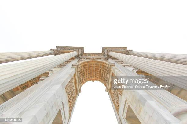 low angle view of triumphal arch against clear sky - arco architettura foto e immagini stock
