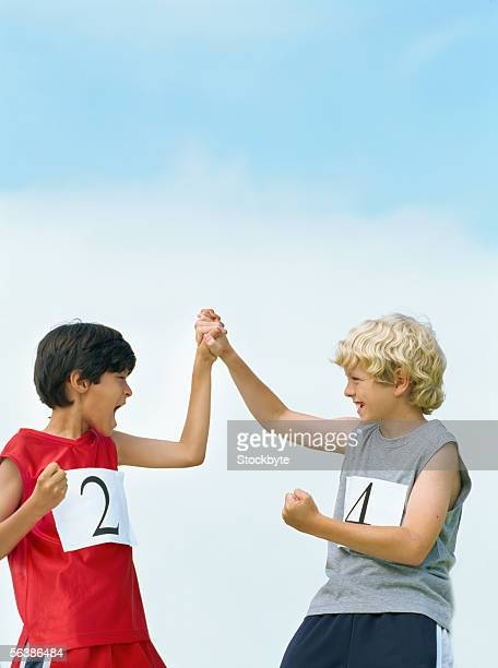 low angle view of two boys raising their hands in victory