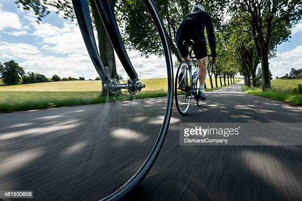 Low Angle View of Two Cyclists Riding Down Country Road