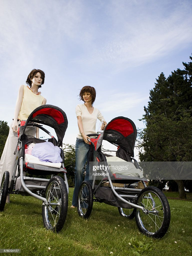 Low angle view of two mannequins portraying mothers pushing prams : Stock Photo
