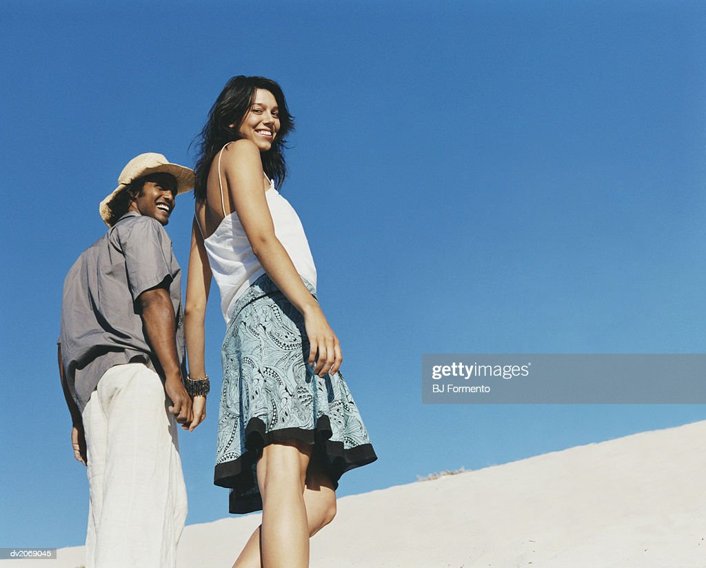 Low Angle View of Two People Walking on a Dune : Stock Photo