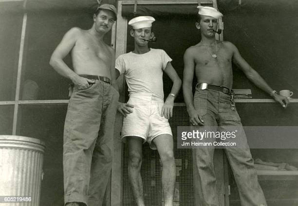 Low angle view of two service bare chested servicemen another in his underwear standing by door of barracks and smoking pipes