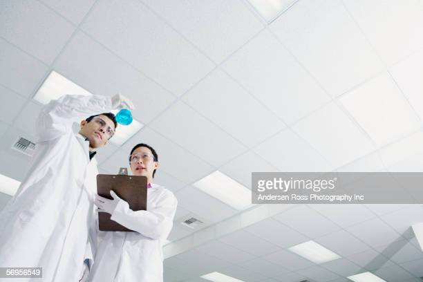 Low angle view of two technicians looking at vial of liquid
