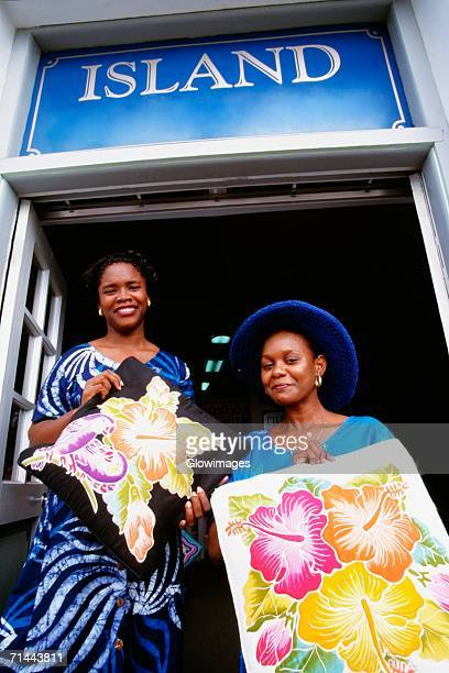 low angle view of two women smiling at the camera, st. kitts - st. kitts stock photos and pictures