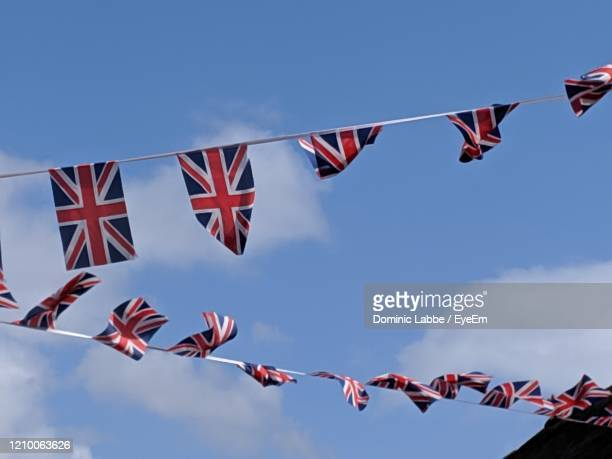 low angle view of uk lowgs hanging against sky - bunting stock pictures, royalty-free photos & images