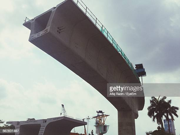 Low Angle View Of Under Construction Bridge Against Cloudy Sky