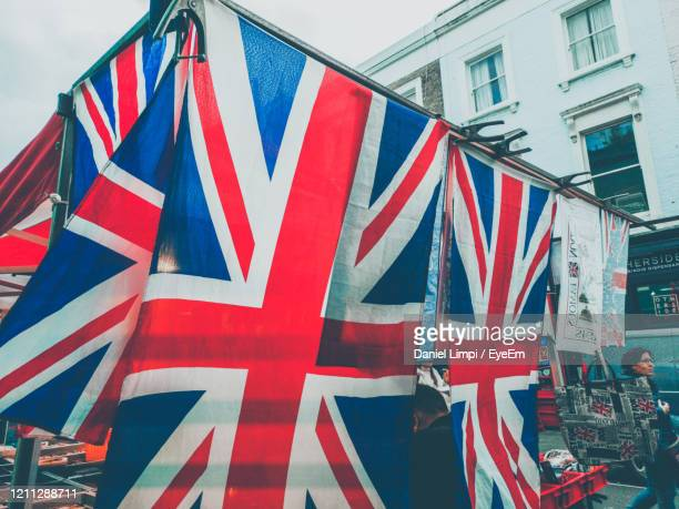 low angle view of union jack flag against buildings in city - referendum stock pictures, royalty-free photos & images