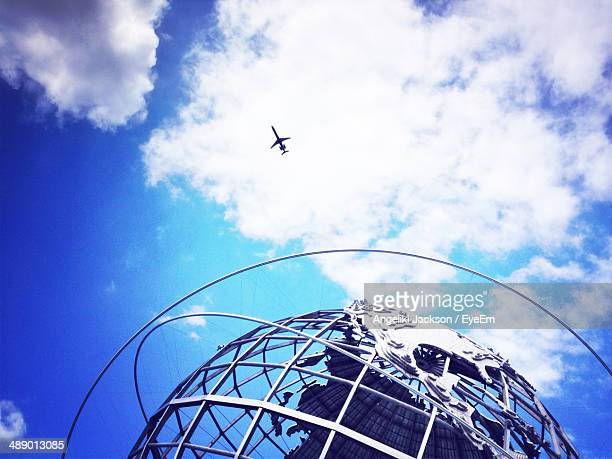 Low angle view of Unisphere and airplane against cloudy sky