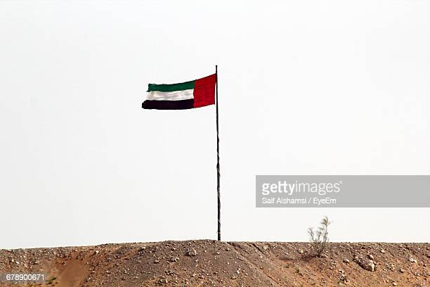 Low Angle View Of United Arab Emirates Flag On Field Against Clear Sky