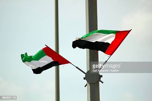 Low Angle View Of United Arab Emirates Flag On Pole Against Sky