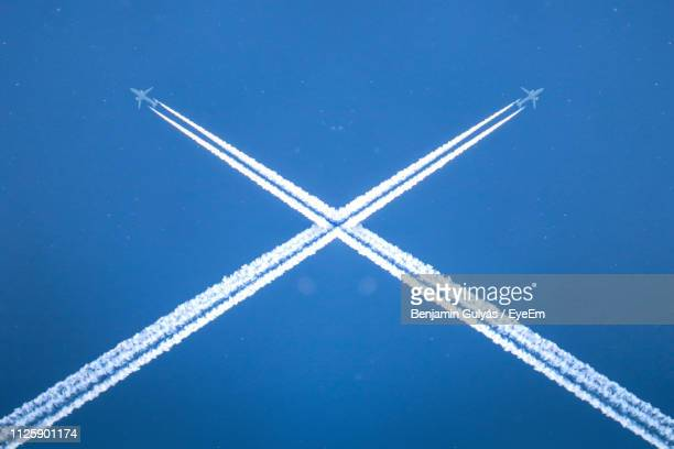 low angle view of vapor trail against blue sky - cross shape stock pictures, royalty-free photos & images