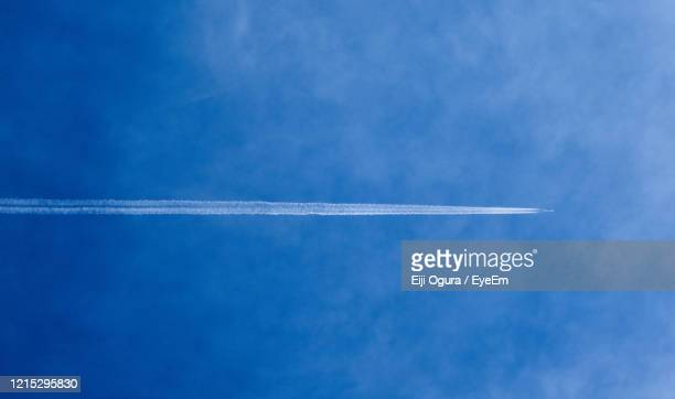 low angle view of vapor trail against blue sky - 航空ショー ストックフォトと画像