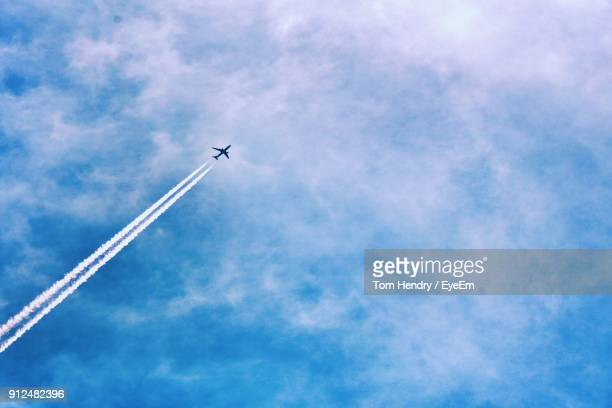 low angle view of vapor trail against blue sky - aeroplane stock photos and pictures