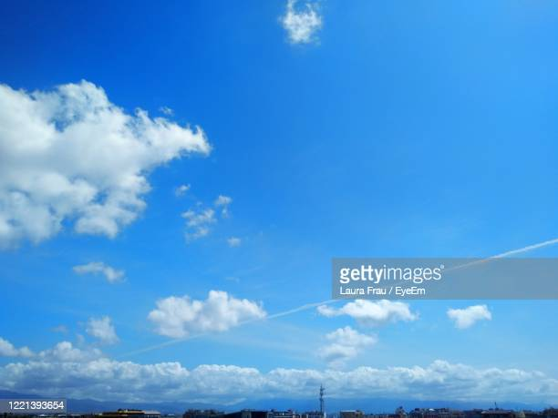 low angle view of vapor trail and white clouds against blue sky - frau photos et images de collection