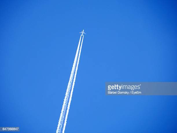 Low Angle View Of Vapor Trail Emitting From Airplane Flying In Blue Sky